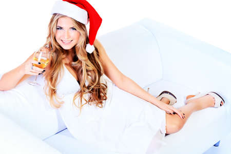 christmas drink: Beautiful blonde woman in festive white dress and christmas hat sitting on a sofa. Isolated over white.