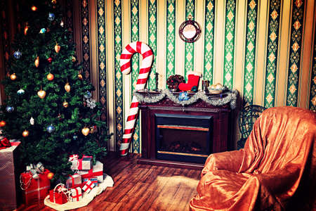 christmas spirit: Christmas home decoration with tree, gifts and fireplace.