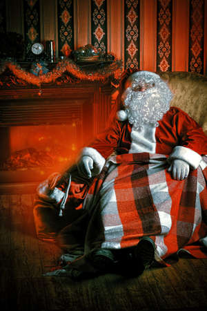Santa Claus having a rest in a comfortable chair near the fireplace at home. Stock Photo - 16797564