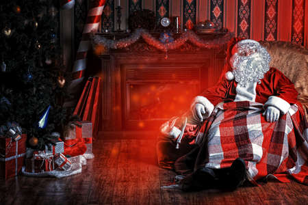 claus: Santa Claus having a rest in a comfortable chair near the fireplace at home.