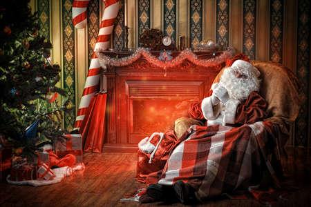 Kerstman met een rust in een comfortabele stoel bij de open haard thuis.