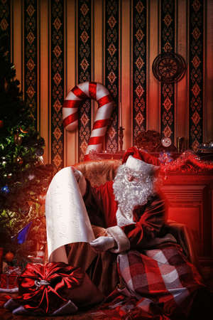 Santa Claus with a list of Christmas presents sitting in a comfortable chair near the fireplace at home.  Stock Photo - 16797586