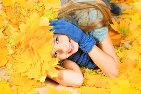 Portrait of a smiling girl in autumn clothes and a hat of maple leaves  photo