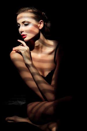 mujeres negras desnudas: Elegante mujer joven posando sobre fondo negro Luz y sombra