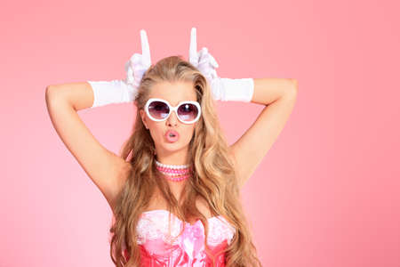 Portrait of a charming blonde woman posing in studio over pink background. photo
