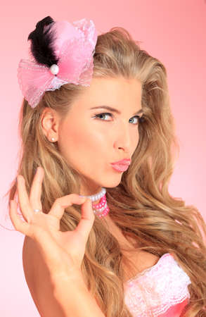 Portrait of a charming blonde woman posing in studio over pink background. Stock Photo - 16848503