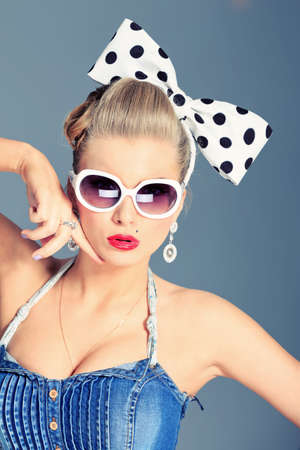 Beautiful young woman with pin-up make-up and hairstyle posing in studio. Stock Photo - 16848506