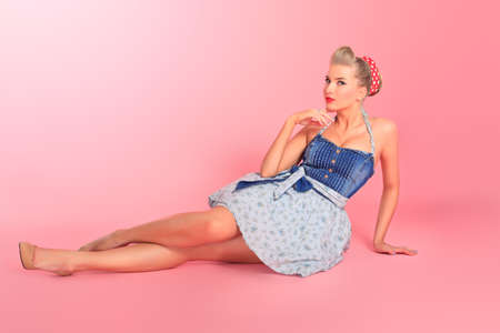 sexy girl sitting: Beautiful young woman with pin-up make-up and hairstyle posing over pink background. Stock Photo