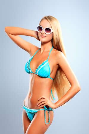 Portrait of a romantic young woman in bikini and sunglasses. Studio shot. Stock Photo - 16884175