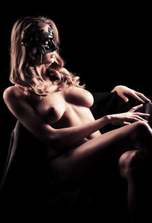 Portrait of a beautiful naked woman in carnival mask posing over black background. Stock Photo