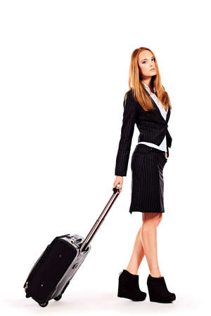 Full length portrait of a successful young business woman standing with travel bag. Isolated over white. Stock Photo - 16884194
