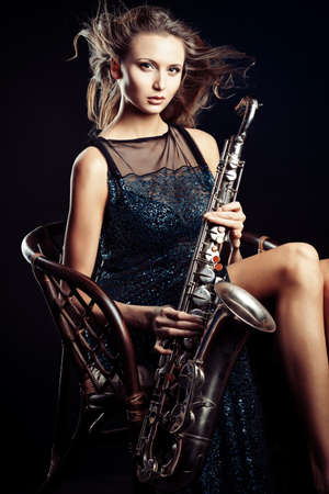 Portrait of a sexual young woman posing with saxophone at studio. photo