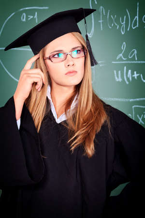 masters degree: Graduating student girl in an academic gown standing at the classroom.