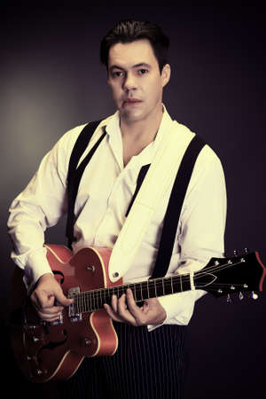 Portrait of a professional artist playing on guitar. Over black background. Stock Photo - 16902001