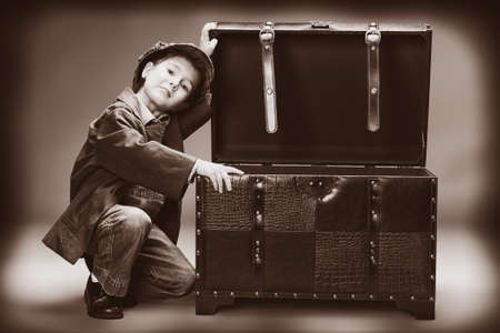 treasure box: Portrait of a cute little boy sitting with a huge old trunk. Vintage style.