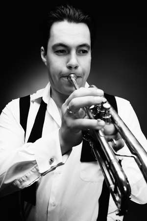 trumpeter: Portrait of a musician playing the trumpet. Black background.