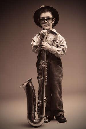Portrait of a cute little boy jazzman playing his saxophone. Retro style. photo