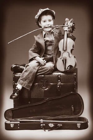 Portrait of a little boy sitting on a big old trunk with his violin and red rose. Retro style. photo