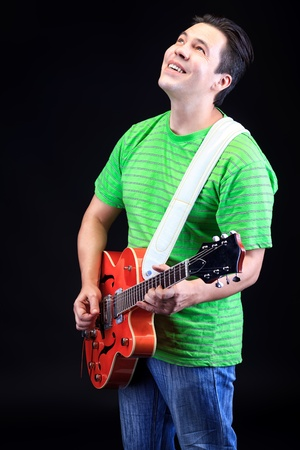 Portrait of a professional artist playing on guitar. Over black background. Stock Photo - 16902030