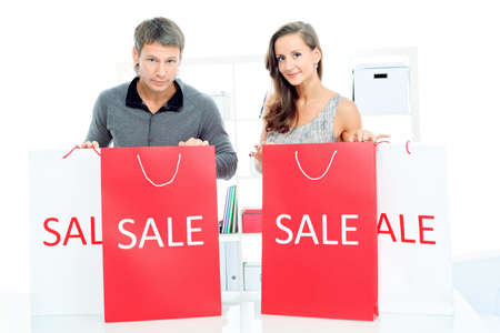 Seasonal sale: happy couple holding shopping bags inside of a store. Stock Photo - 16902009