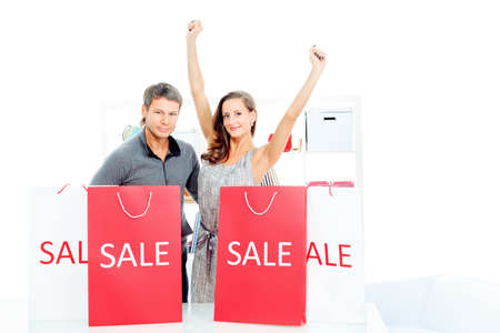Seasonal sale: happy couple holding shopping bags inside of a store. Stock Photo - 16901999