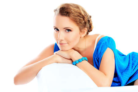 Beautiful young woman in light blue dress sitting on white sofa. Isolated over white. photo