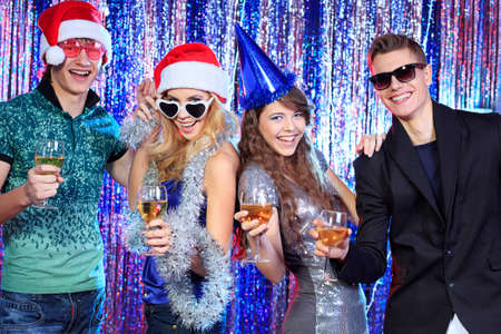 Group of cheerful young people celebrating Christmas at the nightclub. photo