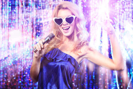 Portrait of a beautiful blonde girl singing with a microphone. Disco lights in the background. photo