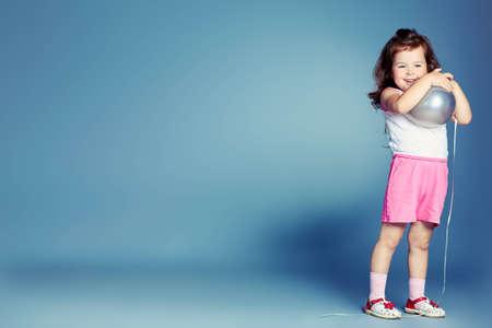 happy children: Pretty little girl over grey background.