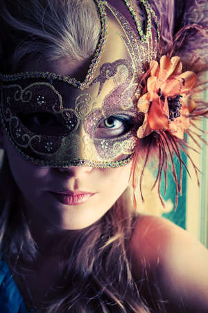 Portrait of a beautiful young woman in a carnival mask. Vintage style. Stock Photo