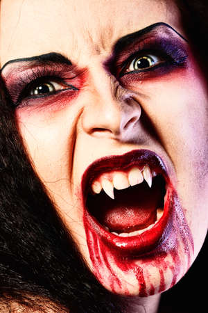 Close-up portrait of a bloodthirsty female vampire. Stock Photo