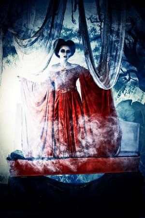 frightening: Bloodthirsty female vampire rises from the coffin on the night cemetery.