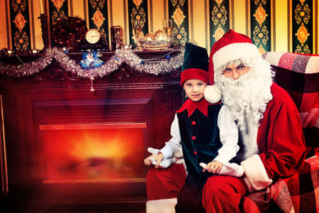 Santa Claus sitting with a little cute boy elf near the fireplace. Stock Photo - 17038911