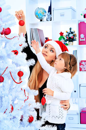 decorating christmas tree: Portrait of a happy mother with her daughter decorating Christmas tree at home. Stock Photo