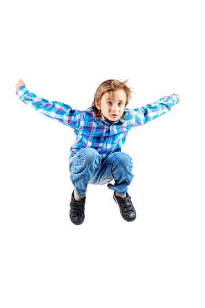 Happy boy is jumping for joy at studio. Isolated over white. photo