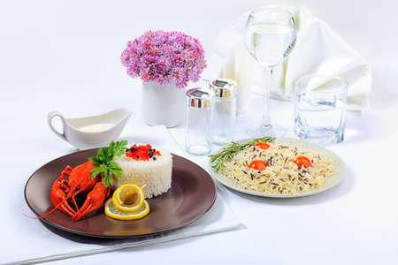 manjar: Mesa de la cena servida con cigalas hervidas, arroz y agua potable. Foto de archivo