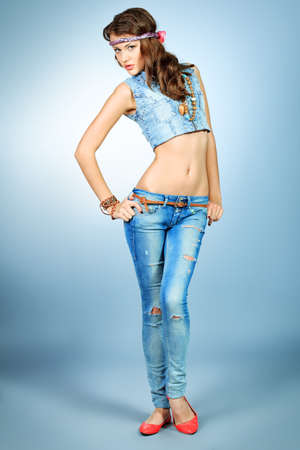 Full length portrait of an attractive young woman in jeans clothing.  photo