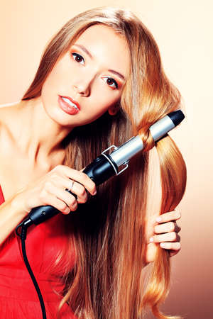 curling irons: Beautiful young woman doing hairstyle with curling irons