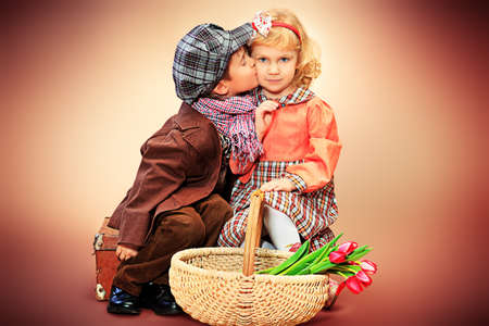 Cute little boy and girl are sitting with a basket of tulips. Retro style. photo