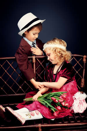 Cute little boy is giving bouquet of tulips to the charming little lady. Retro style. Stock Photo - 17206253