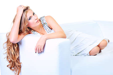 Beautiful young woman with magnificent blonde hair sitting on a sofa. Isolated over white. Stock Photo - 17255341