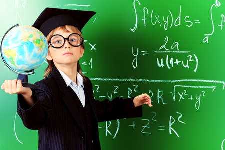 Portrait of a schoolboy in big round spectacles and academic hat at a classroom. photo