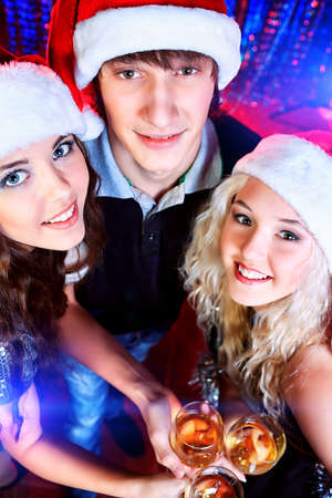 Group of cheerful young people celebrating Christmas at the party. photo