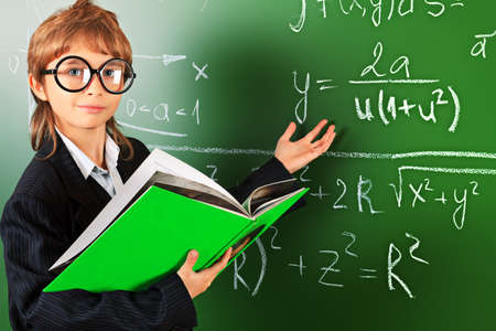 Portrait of a schoolboy in big round spectacles with a book at a classroom. Stock Photo - 17231514