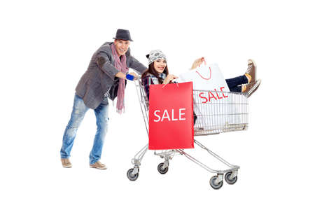 Cheerful couple with a shopping trolley. Isolated over white background. photo