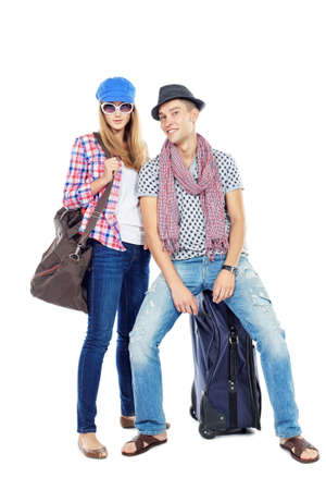 arriving: Pair of cheerful young people standing together with suitcases over white background.