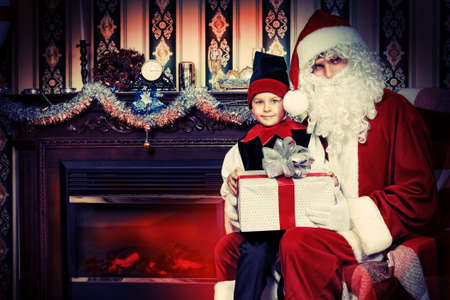 Santa Claus sitting with a little cute boy elf near the fireplace. photo