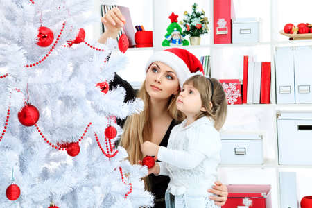 Portrait of a happy mother with her daughter decorating Christmas tree at home  photo