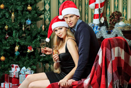 Happy young couple celebrating Christmas near the Christmas tree and fireplace at home  photo