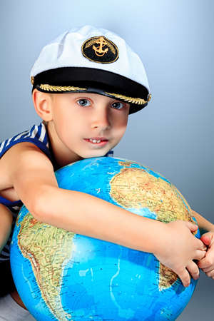 Little sailor boy standing with the globe. Stock Photo - 17305076